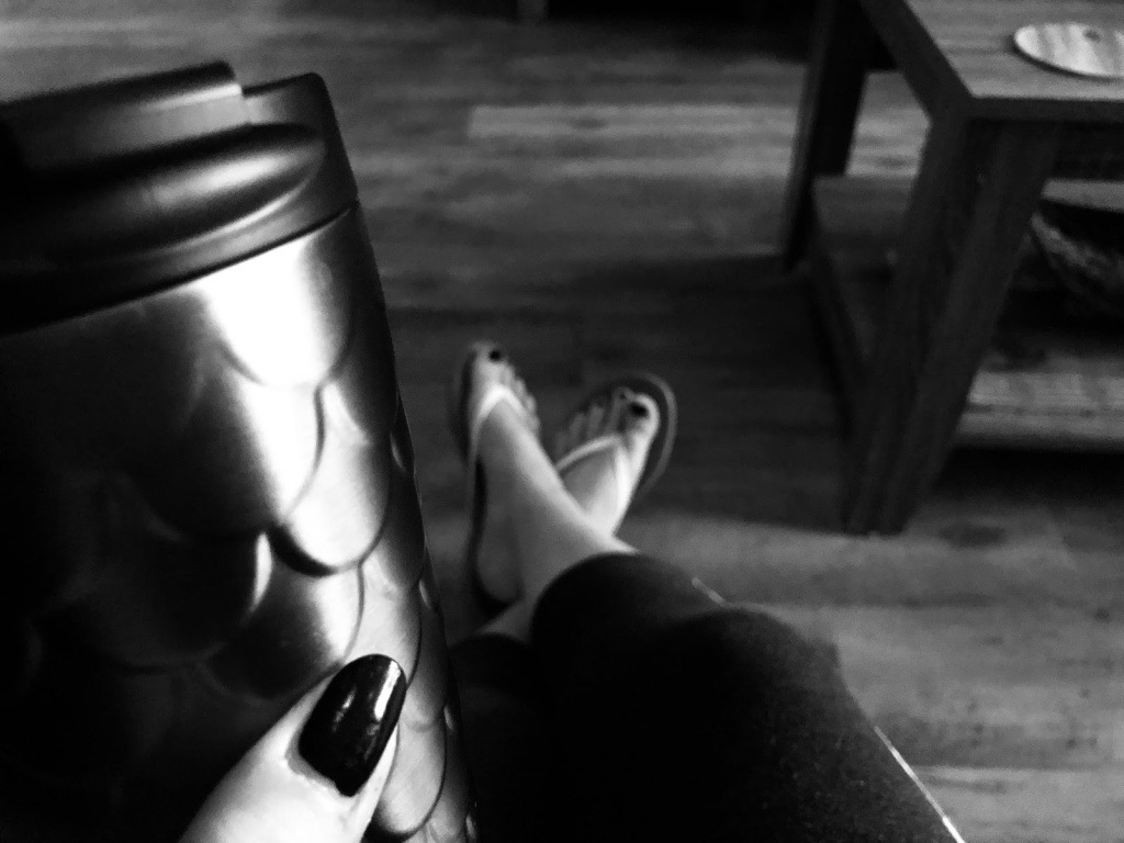 a scalloped coffee thermus being held by a hand with black nail polish, in the distance feet are stretched out into room