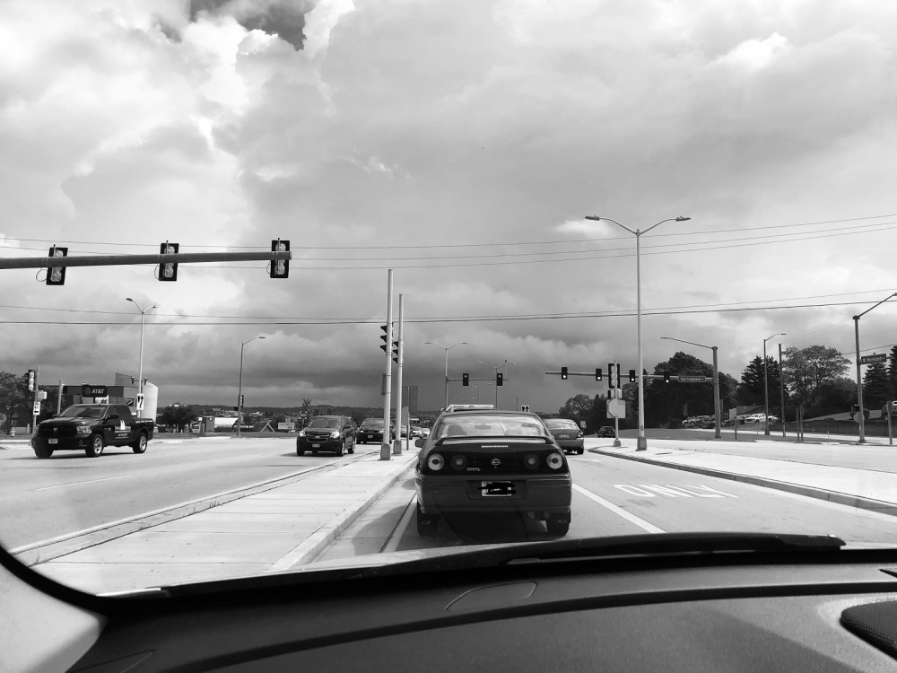 a black and white photo of cars stopped at a traffic light, storms appear to be brewing in the distance.