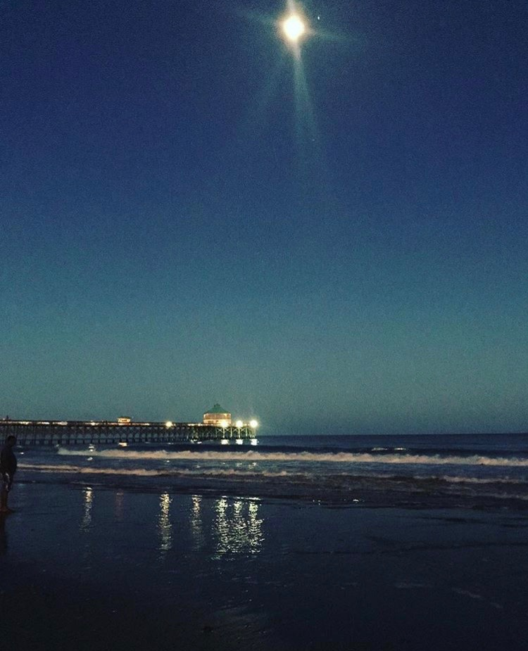 A very clear blue night sky with the full moon shining bright over the top of an illuminated pier extending over the ocean.