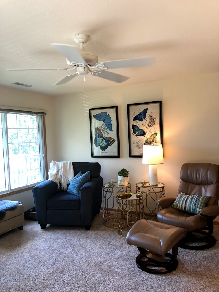 Two accent chairs paired along a wall, one in deep navy the other a soft brown leather/tan tone with a trio of gold nesting tables arranged between them. A white lamp sits on top of one of the tables. Two butterfly paintings are centered above the chairs.