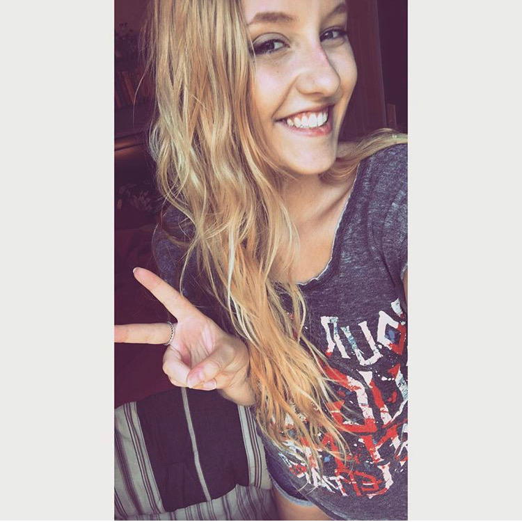 photo of white woman with long wavy blonde hair, sunkissed skin and visible freckles throwing up a peace sign while smiling and wearing a def leppard tshirt