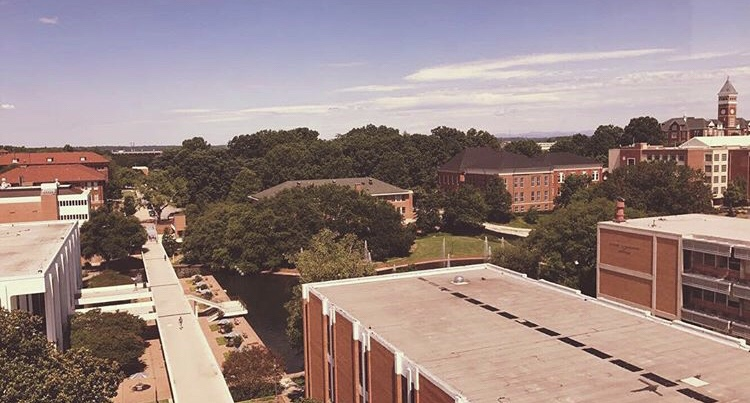 aerial view of clemson univeristy showing the tops of buildings and the library with the large clocktower in the distance