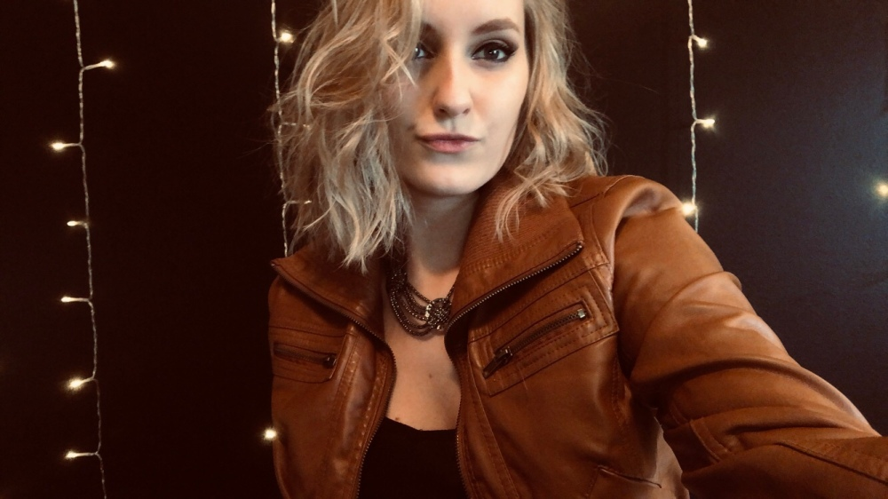 white woman with short blonde hair wearing a brown leather jacket. The walls behind her are painted black and have string lights dangling around her.