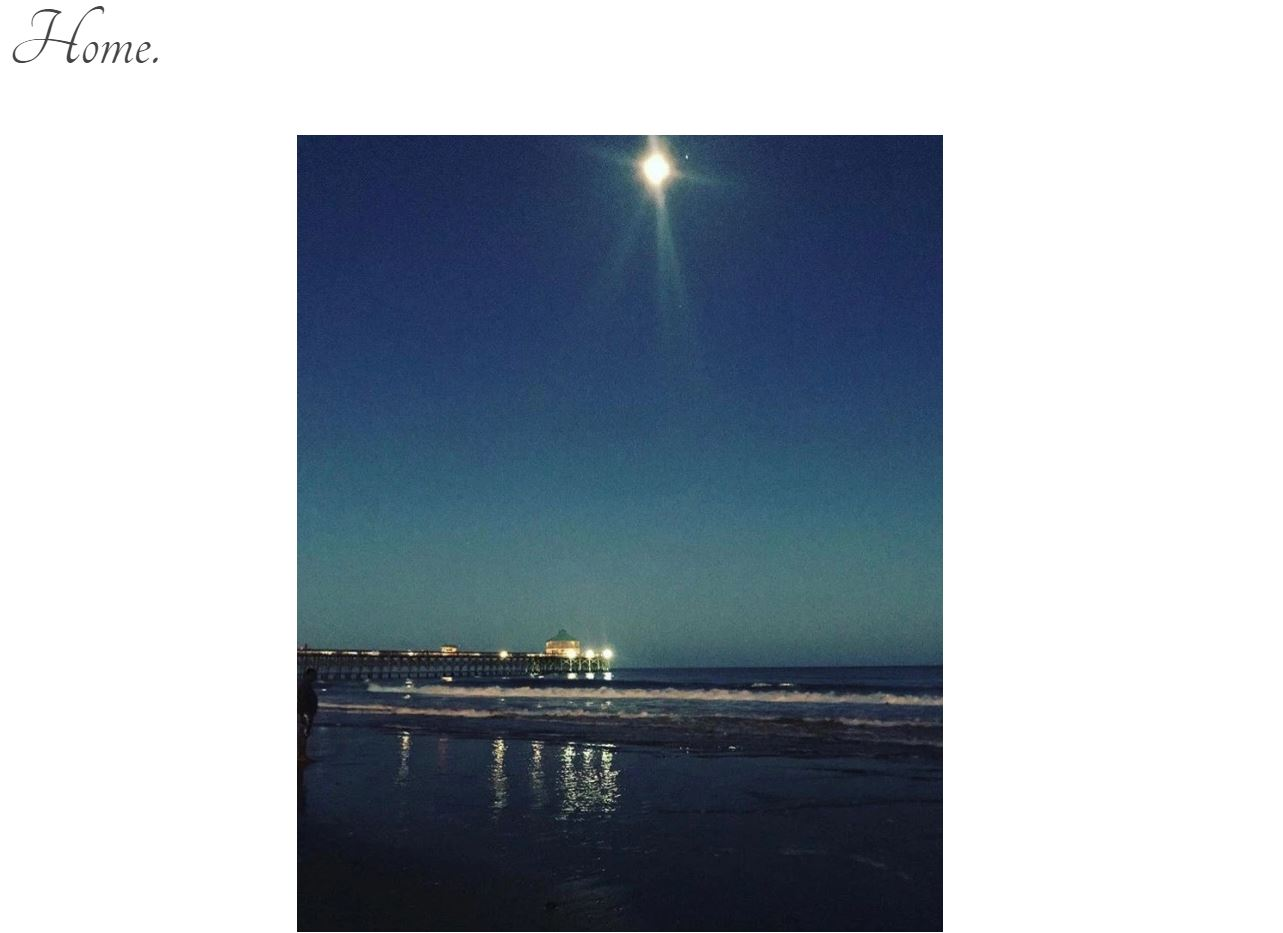 "Screen grab of blog title page: ""Home"" with a photo taken at night of the moon hanging high above the pier that is illuminated by lights. The waves are gently crashing against the sandy beach."