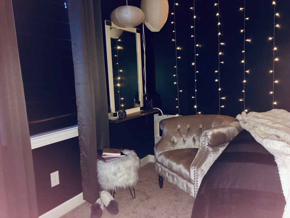 a black bedroom showing a vanity area with a large champagne colored chair and a white furry ottomon against a backdrop of hanging lights. The curtains are dark grey and pulled shut.