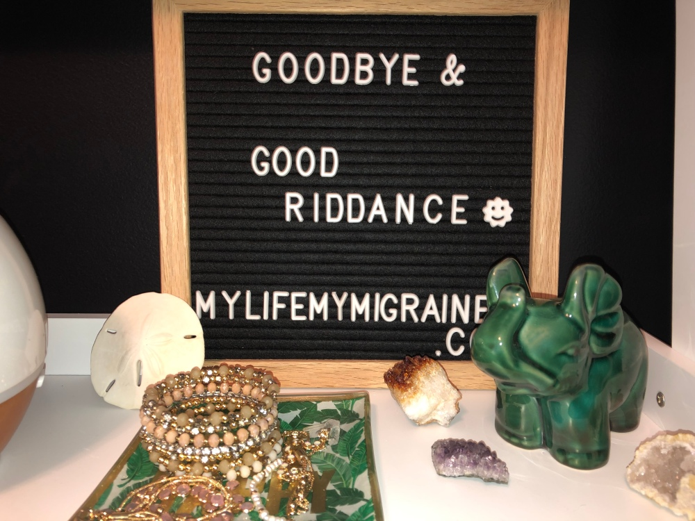 "black felt board spelling out ""goodbye and good riddance"" with various crystals and jewerly in the front of the picture."
