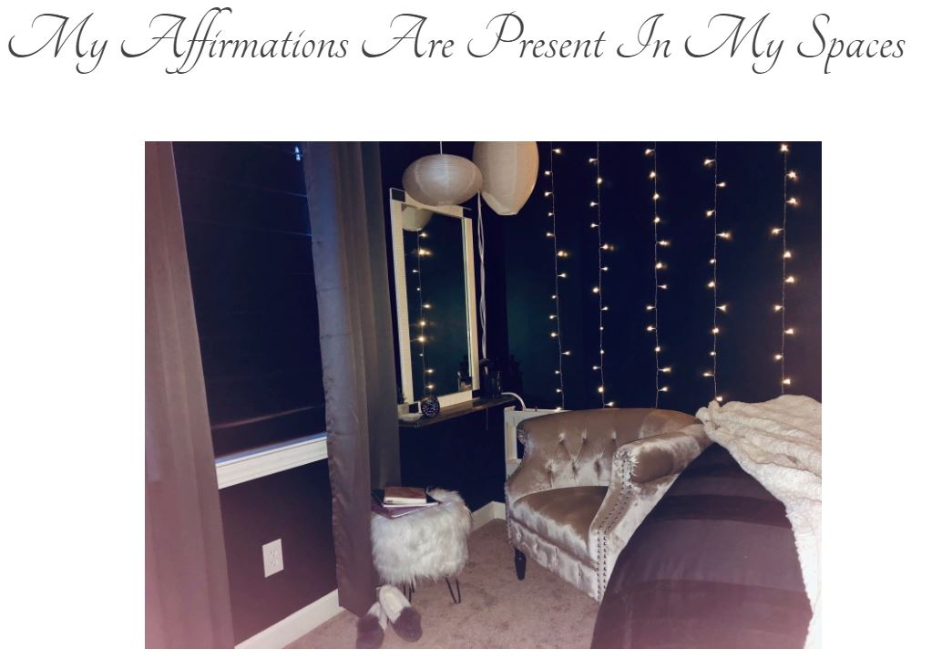 "Screen grab of blog title page: ""My Affirmations Are Present In My Spaces"" with photo of a bedroom with black walls, focusing on a blush velvet chair sitting at a vanity with twinkly lights along the wall."