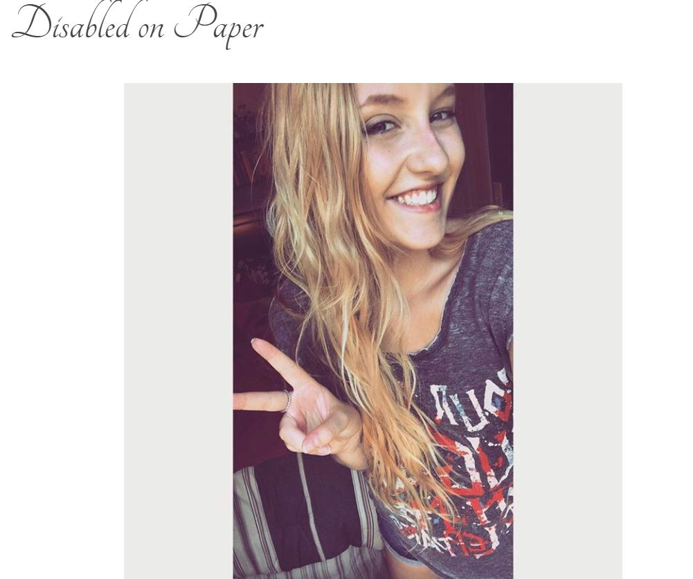 "Screen Grab of blog title page: ""Disabled on Paper"" with a photo of a blonde girl with long hair with beachy waves, freckled skin, holding up a peace sign wearing a Def Leppard T-shirt. She's smiling in this photo."