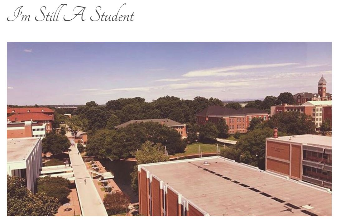 "Screen grab of blog title page: ""I'm Still A Student"" with a photo of Clemson University's campus looking down upon the white library and orange toned brick buildings."