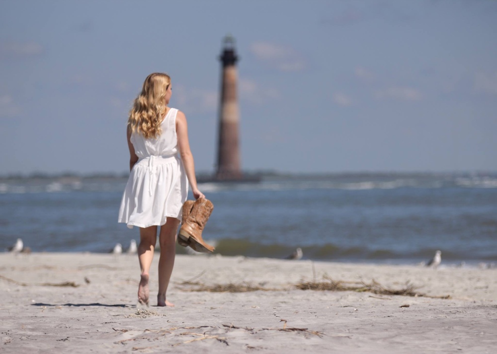 White woman with long blonde hair wearing a knee length white dress holding a pair of cowboy boots walking away from the camera, barefoot on the beach. There's a lighthouse in the distance.
