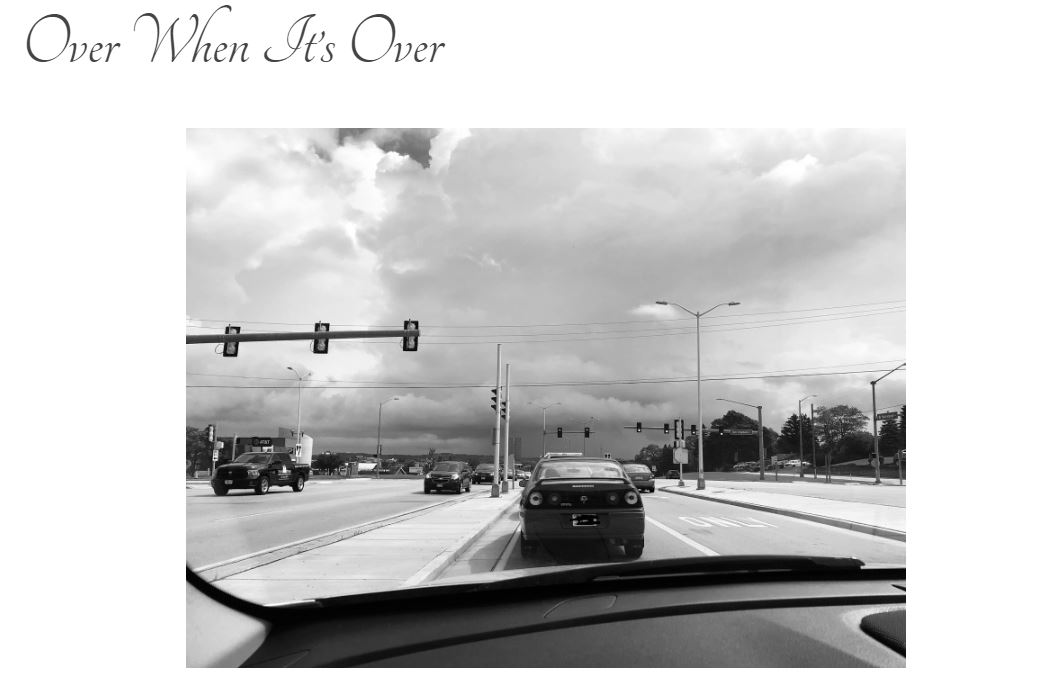 "Screen grab of blog title page: ""Over When It's Over"" with black and white photo of cars sitting in traffic with dark skies in the distance."