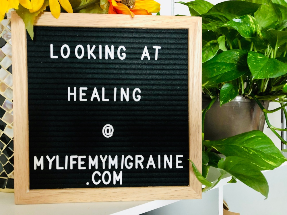 "Black felt board with text ""looking at healing"" with a large green pothos plant behind it."