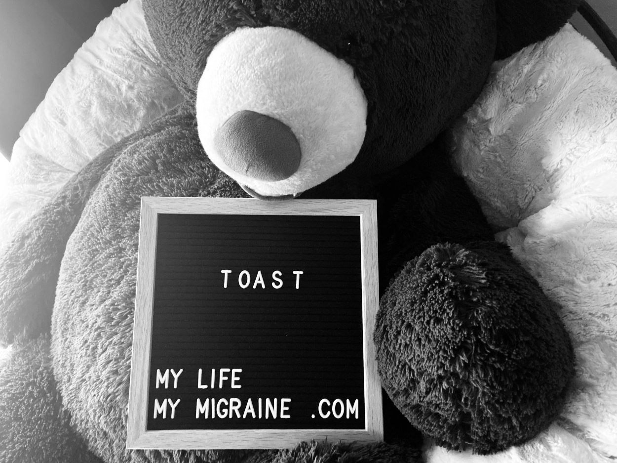 """Black and white image depicting a large teddy bear holding a felt board sign that says """"toast"""""""