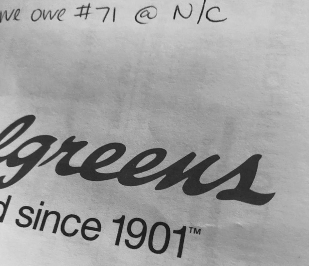 "Cropped image of a Walgreen's prescription paper bag with a handwritten note ""we owe #71 at no cost"" across the top."