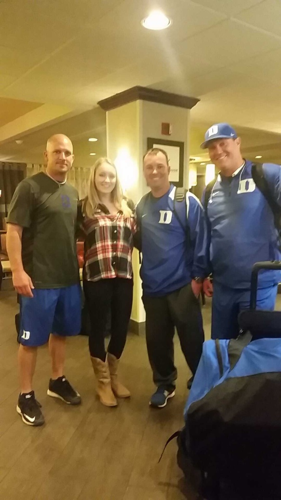 Girl in flannel and cowboy boots posing for photo with three staff members on the Duke Baseball team.