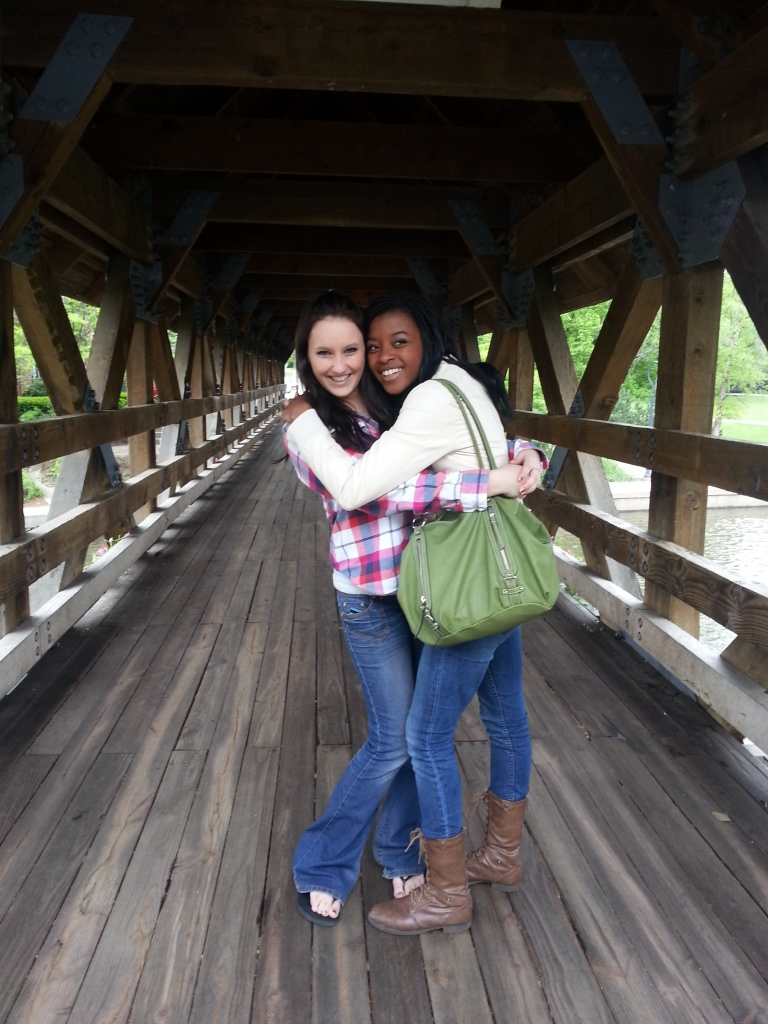 Two girls hugging each other on a bridge laughing.