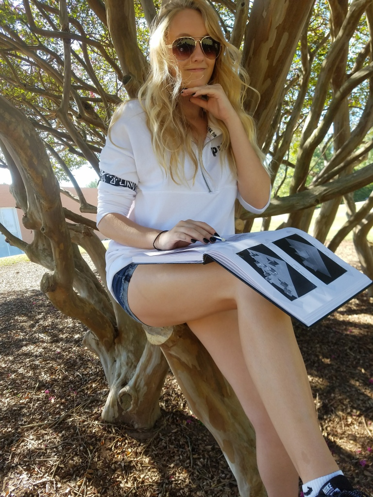 Girl in white pullover and shorts, sitting in a tree with a sketchbook in her lap.