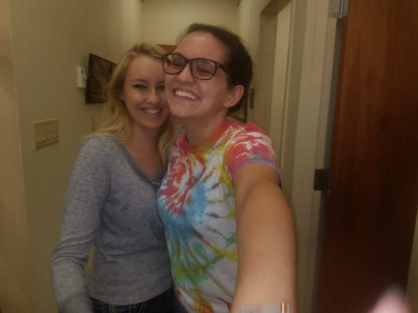 Two girls posing and laughing in a hallway. One is in a grey shirt, the other a tye-dye t-shirt.