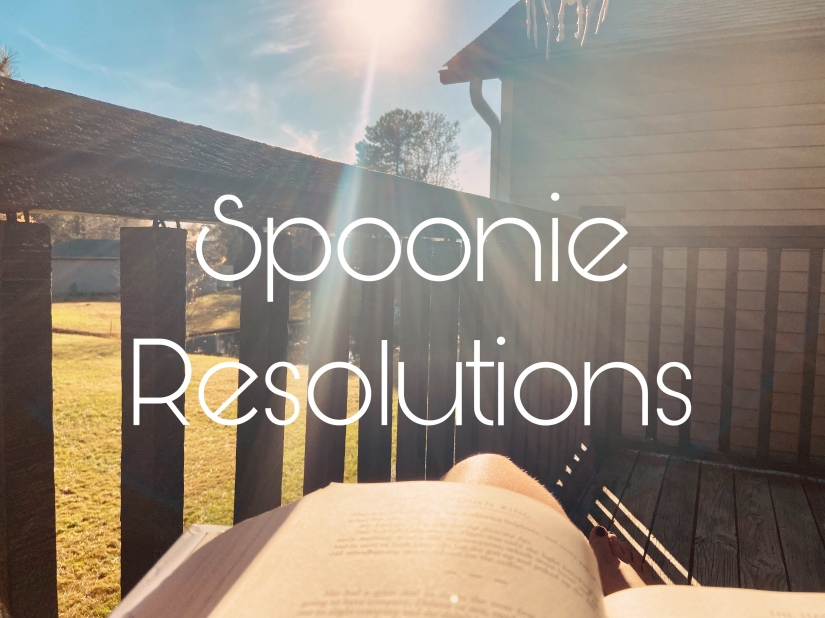 image text: spoonie resolutions image background: looking down on a book with the sun shining down overlooking a small pond and some trees through a wooden balcony.