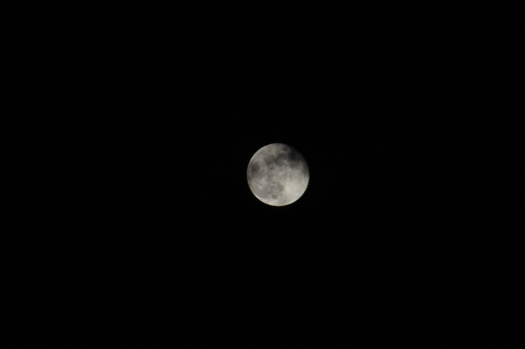 Full moon slightly covered in clouds.