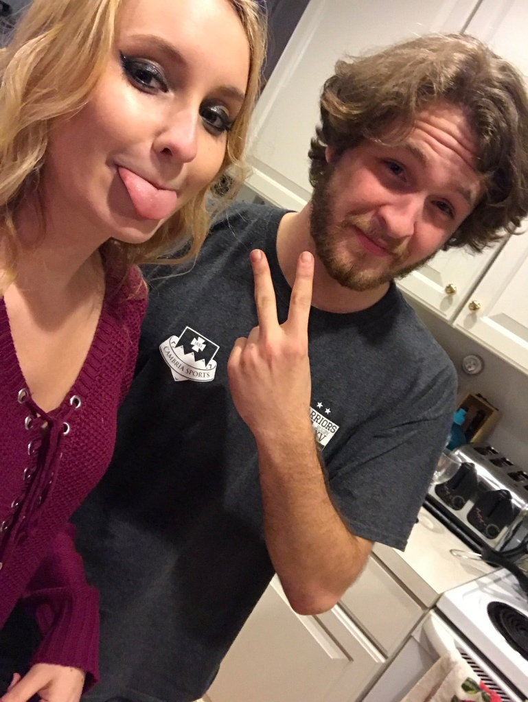 Blonde girl sticking out her tongue, brunette guy with shaggy haircut throwing up a peace sign.