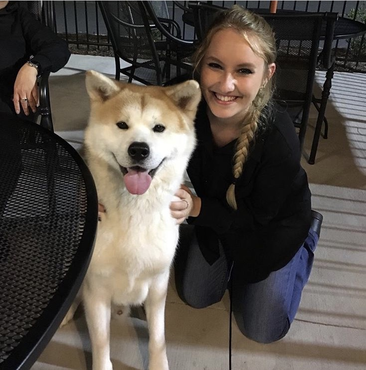 Girl with long braid posing with an Akita breed of dog.