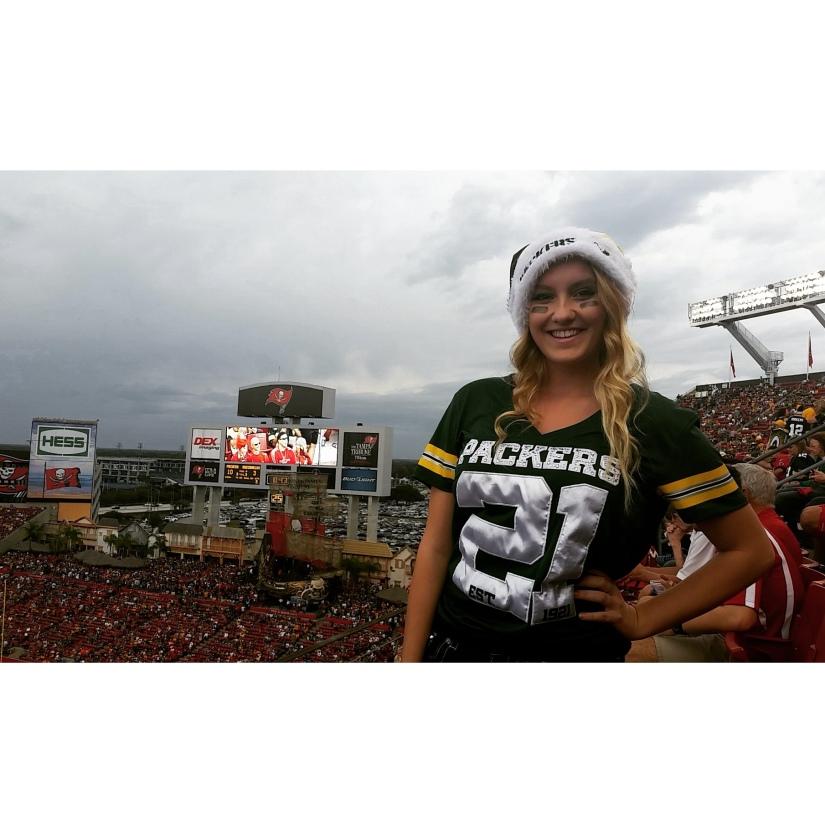 Blonde girl wearing a packers christmas hat and jersey with the Tampa Bay Buccaneers stadium in the background.