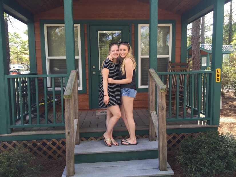 Two girls posing in front of a log cabin rental.