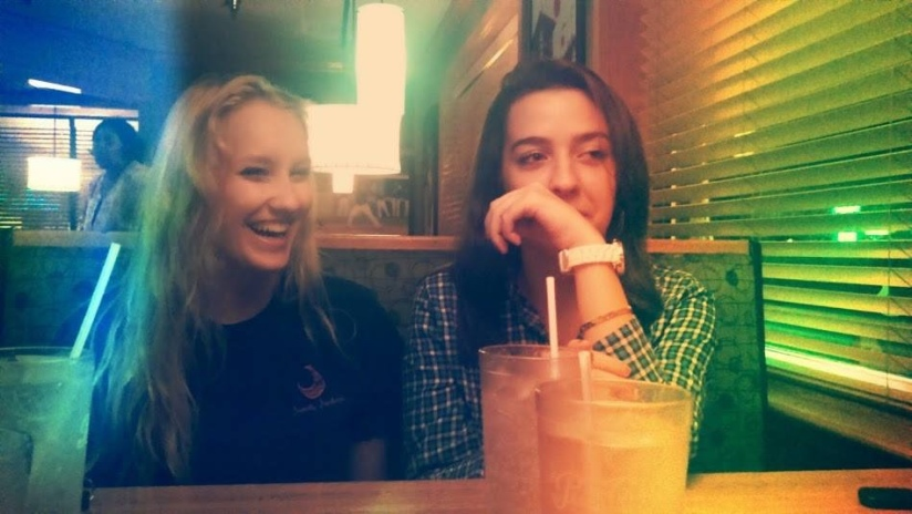 Two girls sitting at a table in a restaurant laughing over drinks.