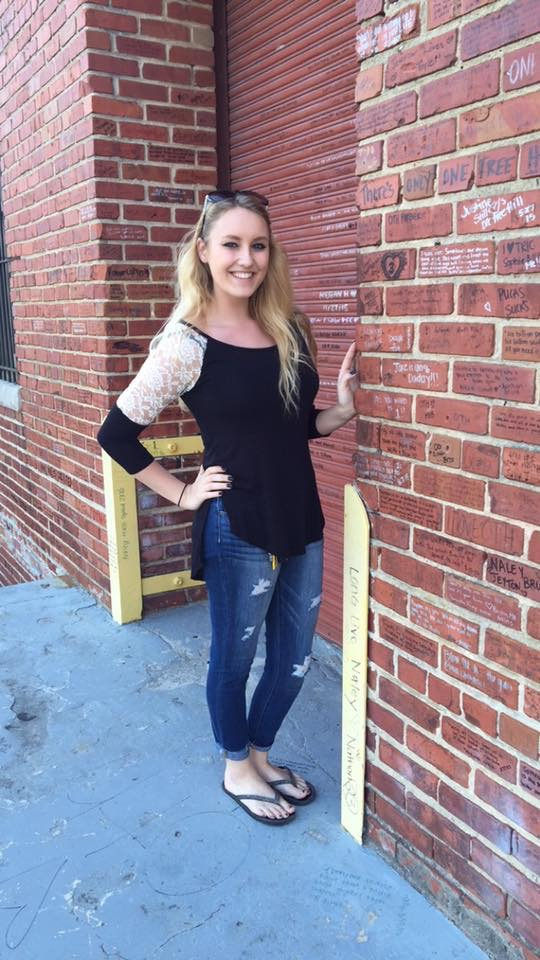 Girl in a black top and jeans standing against a brick wall on the set of One Tree Hill.