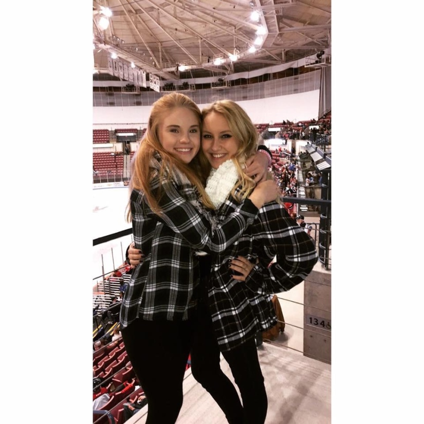 Two girls in matching flannels hugging at a hockey game.