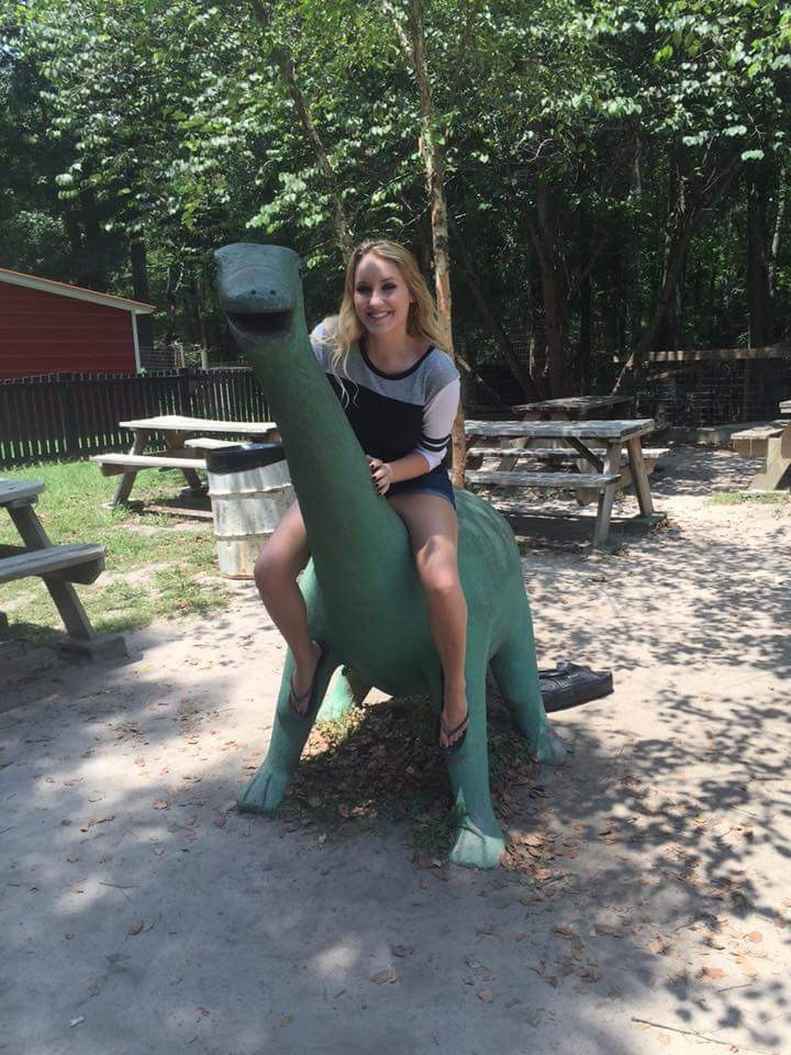Blonde girl sitting on top of a long neck dinosaur.
