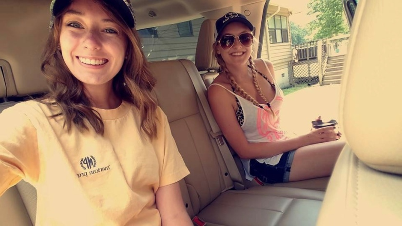 Two girls posing in the back of the car dressed to head out on the lake for the day.