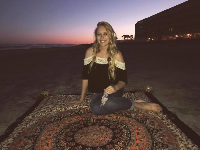 Blonde girl in summery black shirt with lace trim sitting on a mandala printed tapestry on the beach with the sun setting behind her.