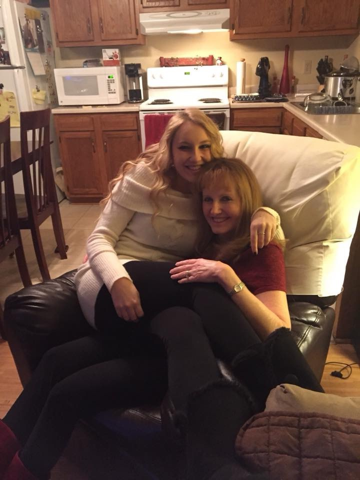 Photo of blonde girl sitting on top of her mother, squishing her before a holiday party.