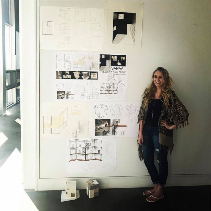 Girl standing next to a large wall full of architectural drawings on display with models on the floor.