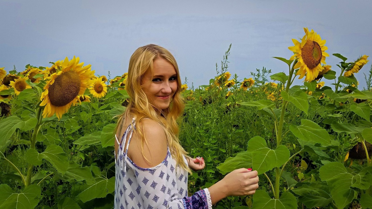 blonde girl standing in a field of sunflowers looking back at the camera.
