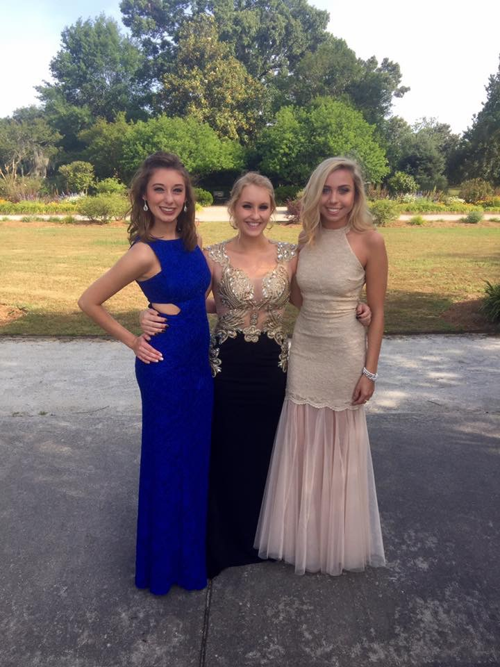 Three girls in prom dresses posing for professional photos.
