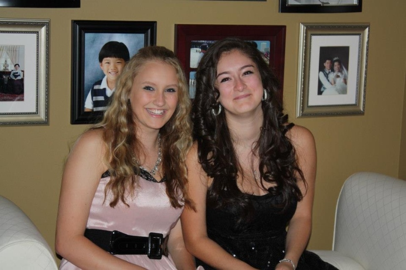 A blonde and brunette girl both dressed up in nice gowns sitting on a couch having homecoming photos taken.