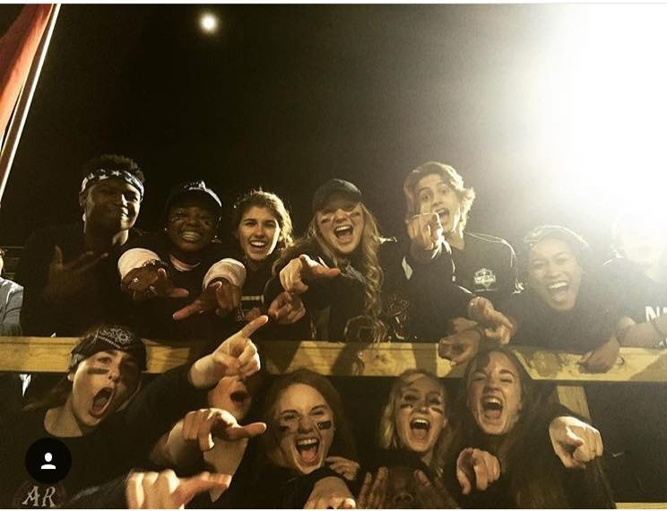 Large group of students all wearing black screaming down into a camera during a football game.