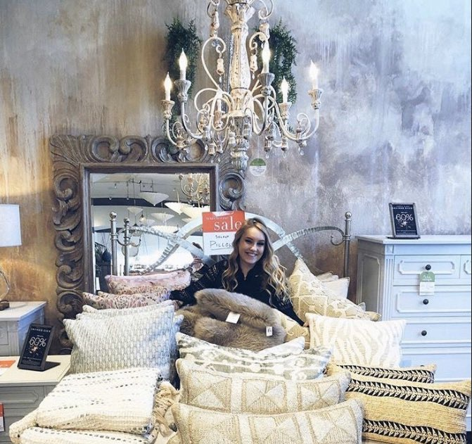 Girl sitting on a bed of pillows.