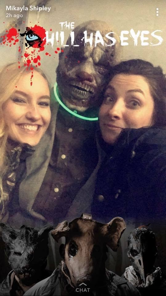 Two girls bundled up in the cold with a person dressed in a mask at a haunted outdoor event.