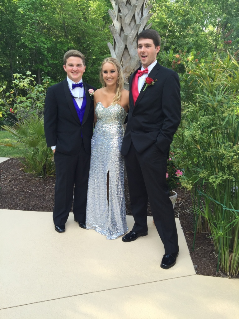 Girl in silver prom dress posing with two gentlemen in tuxes.