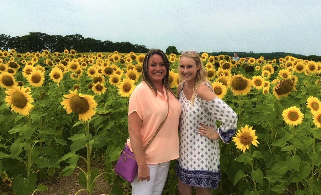 Two sisters standing in front of a very large sunflower field.