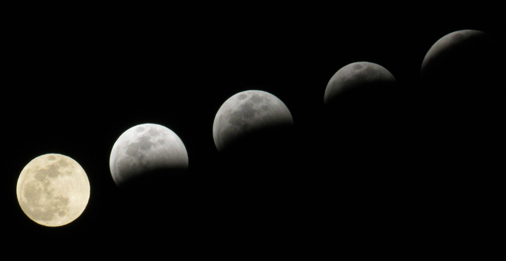 composite image of the full moon during five stages of a lunar eclipse.