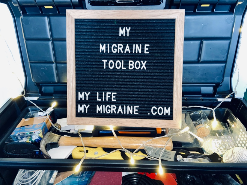 "A black felt board with white letters spelling out ""my migraine toolbox"" propped in an actual toolbox full of hammers and tacks and decorative lights."