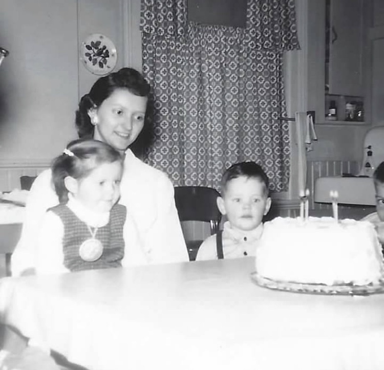 Black and white photo from the late 50s of a mother with her daughter sitting on her lap ready to blow out candles on a birthday cake. A young boy is sitting next to the mother.