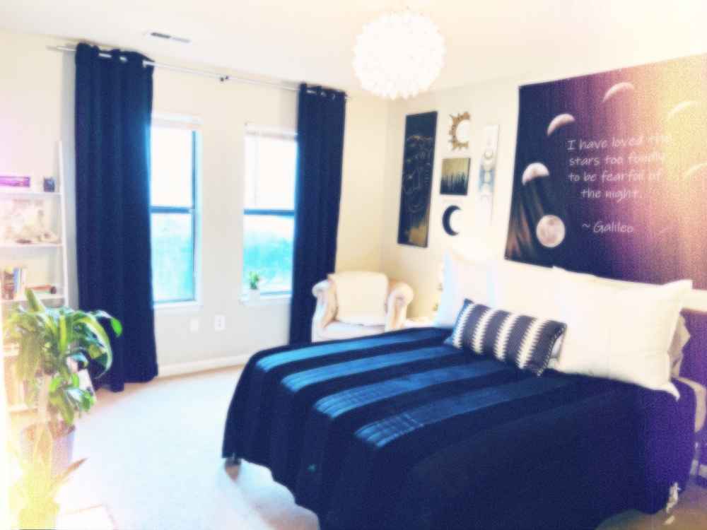 Slightly blurred image of bedroom with black striped bedding and large white euro pillows. The wall behind the bed is covered in black, white, and gold artwork. The windows are framed with long black curtains. There's a white lotus capiz shell chandelier hanging above the bed and a few plants throughout the space.