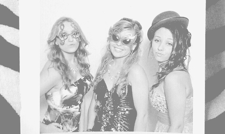 Black and white clipping of a photobooth printout with three girls in fancy gowns wearing funny glasses.