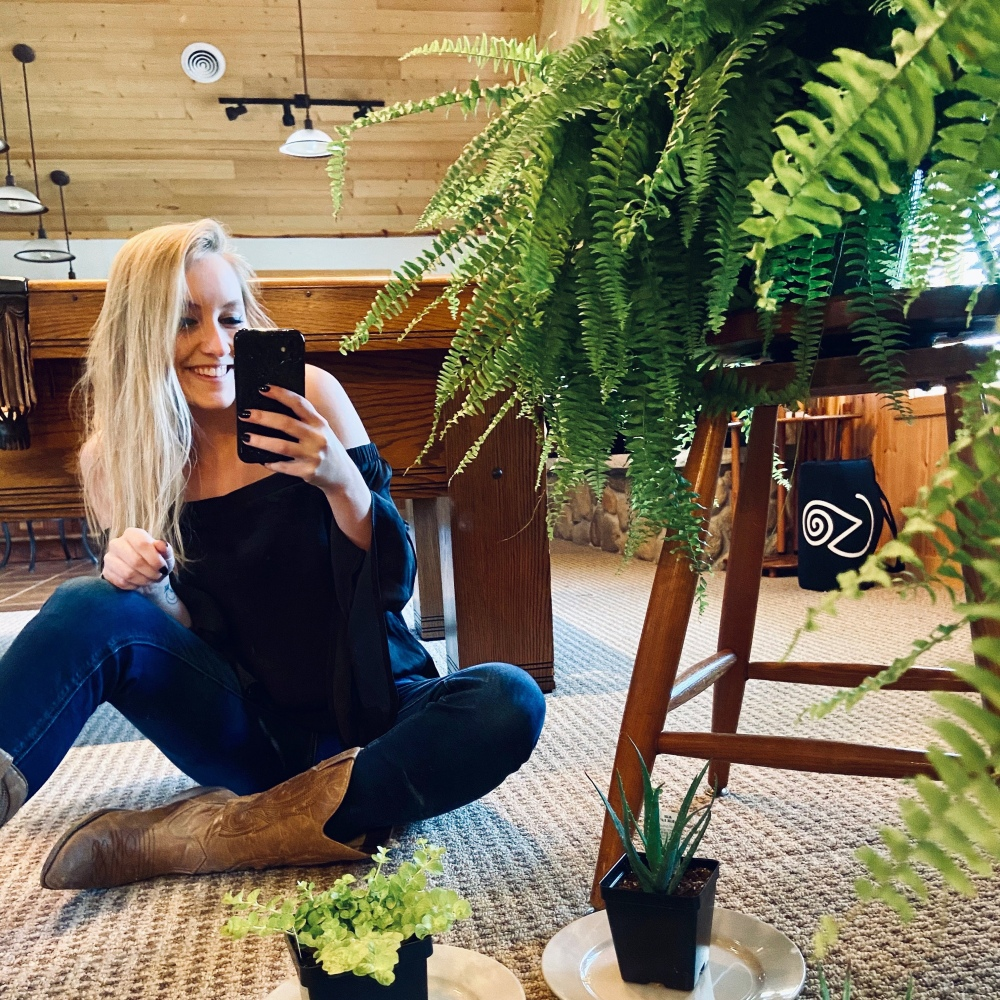 Woman with blonde hair sitting on the floor next to a large fern perched on a stool